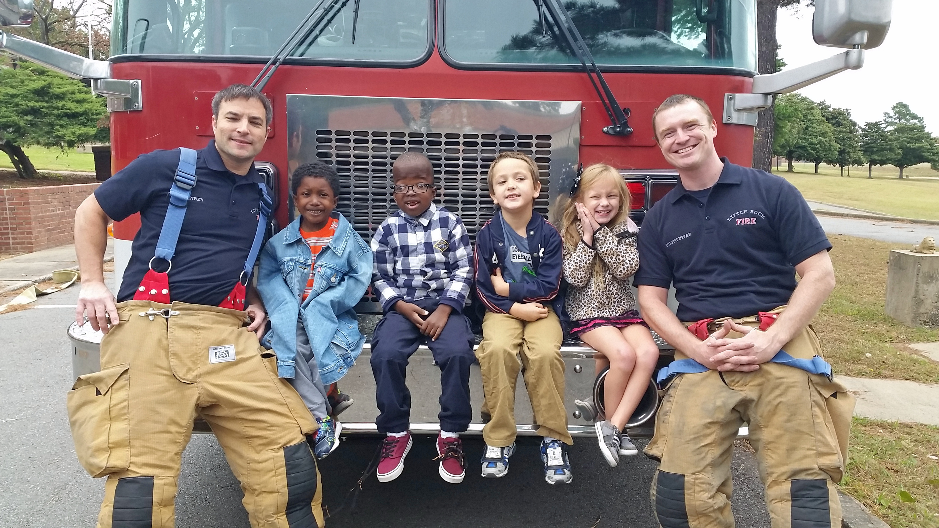 Students and Little Rock firemen sitting on the front bumper of a fire truck.